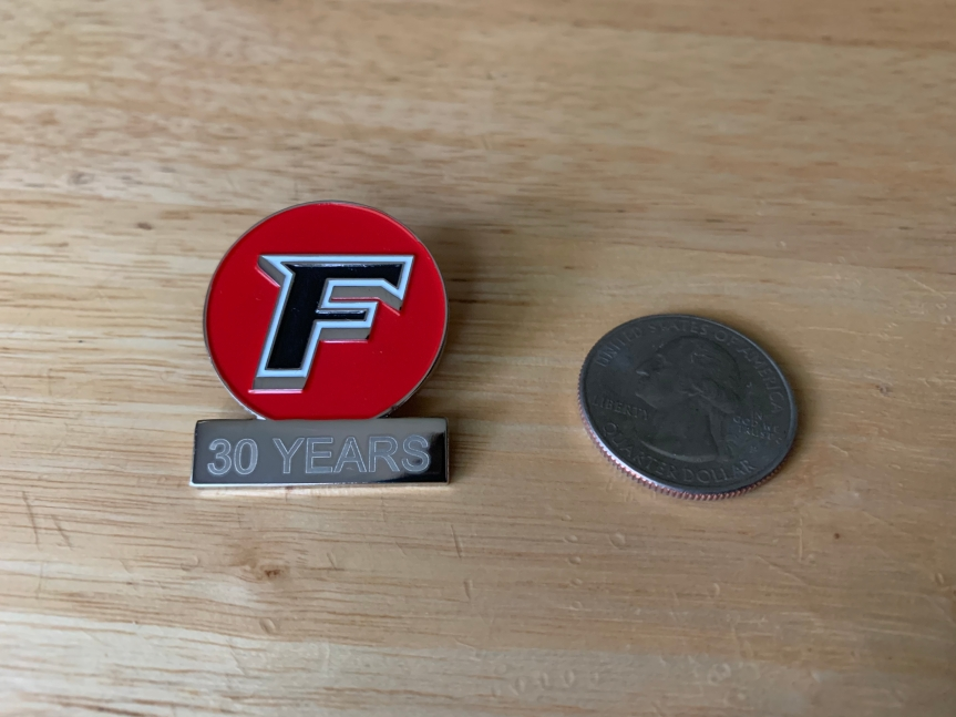 Professor Receives Small Metal Pin from University for Thirty Years ofTeaching